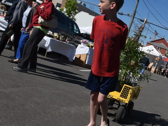 Kylan Hansen of Sturgeon Bay pulls a newly purchased wisteria bush held by little brother Siggy in the back for his grandmother Janice Smits of Sturgeon Bay during the opening Saturday of the Sturgeon Bay Farmers and Craft Market.
