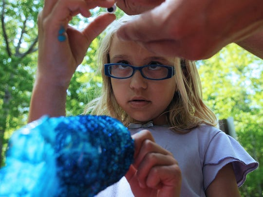 "Tina says: It's a staredown — a plastic eye was a mirror image of Natalie Raschka's as she constructs a fish art project during ""Fishy Activities"" on June 7 at Peninsula State Park."