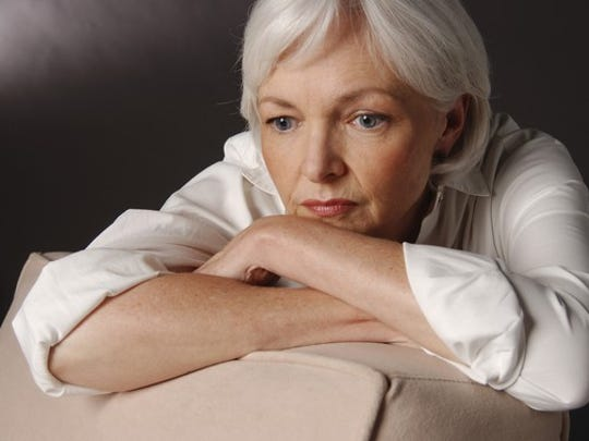 A worried senior woman with her chin on her propped-up arms resting on the back of a chair and staring blankly ahead
