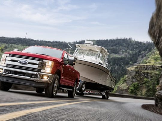 A red 2018 Ford F-250 Lariat, a big pickup truck, is shown towing a boat trailer up a mountain road.
