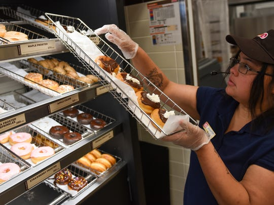 Jennifer Ruiz, manager of Dunkin' Donuts, places donuts on the rack at the  new Dunkin' Donuts that opened up at 1980 Quentin Road.
