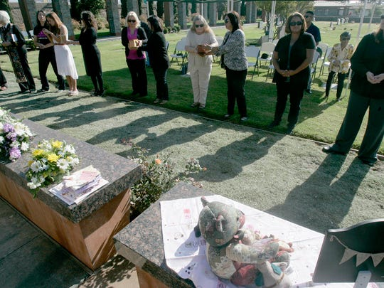 People attending a memorial service for abandoned babies pass the babies' urns Saturday at Ivy Lawn Memorial Park.
