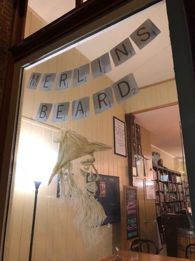 The sign on the outside window of Merlin's Beard on
