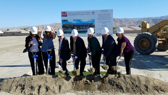Desert Sands Unified School District officials participate in a groundbreaking ceremony on a windy day. Pictured are (left to right) board member Wendy Jonathan, Indio Mayor Elaine Holmes, superintendent Scott Bailey, board president Donald Griffith, board vice president Gary Tomak, and board members Michael Duran and Linda Porras.
