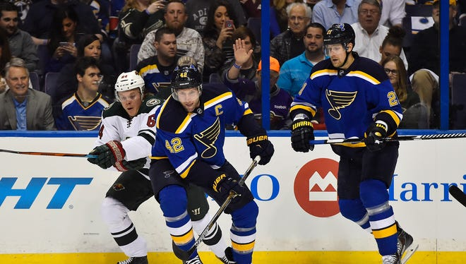 St. Louis Blues center David Backes (42) controls the puck under pressure from Minnesota Wild center Mikael Granlund (64) in the first period in game one of the first round.