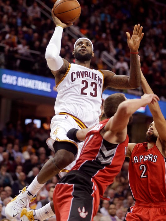 Cleveland Cavaliers' LeBron James (23) shoots over Toronto Raptors' Landry Fields (2) and Jonas Valanciunas in the fourth quarter of an NBA basketball game Tuesday, Dec. 9, 2014, in Cleveland. James scored 35 points to lead the Cavaliers to a 105-101 win. (AP Photo/Mark Duncan)