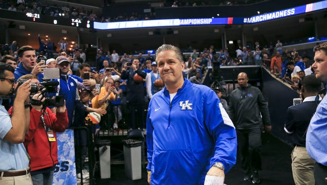 Kentucky's John Calipari walks towards the court admist boos and cheers before Sweet Sixteen practice at the FedExForum in Memphis Thursday afternoon. 'It was a special time' Calipari said about his time as Memphis' head coach. 'I understand some people were upset that I left. It's kinda special to be back.'