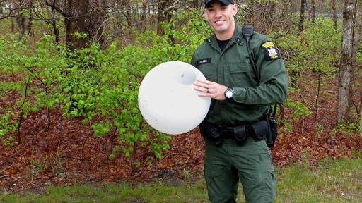 In this May 3 photo provided by the New York State Department of Environmental Conservation, Environmental Conservation Officer Jeff Hull holds a globe from a lighting fixture that he helped remove from a deer's head in Centereach, N.Y. Hull answered a call about the mammal in distress and was able to help it free itself after wrestling with it a couple times. The deer ran into the woods once the globe came off.