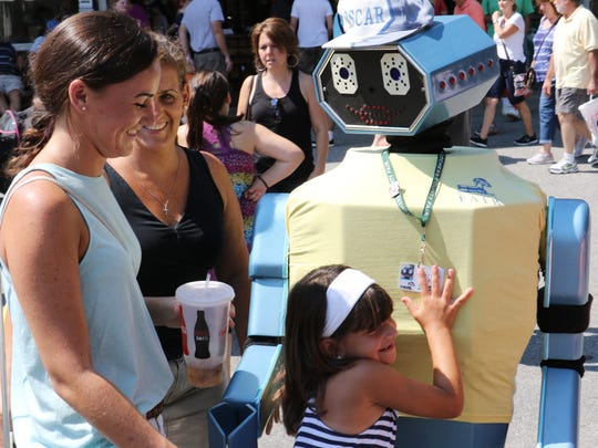 From left, Alyssa, Madison, and Debbie McNally, of the Town of Poughkeepsie give Oscar T Robot a hug at the Dutchess County Fair in Rhinebeck on Tuesday.
