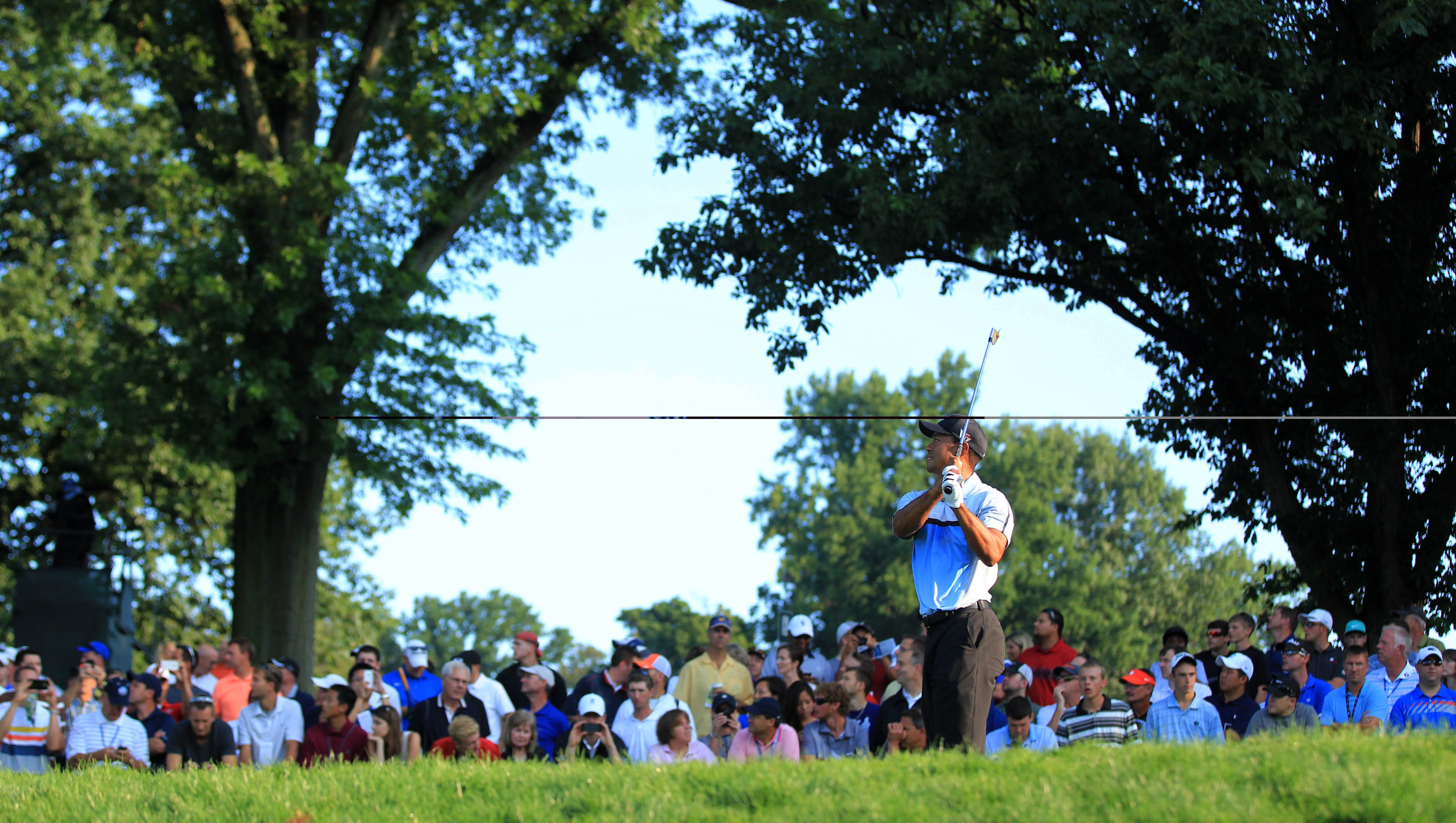 Tiger Woods warms up on the practice range before the first round of the 95th PGA Championship at Oak Hill Country Club.