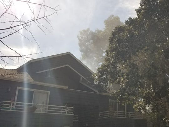 Smoke rises from a fire on the second floor of an apartment