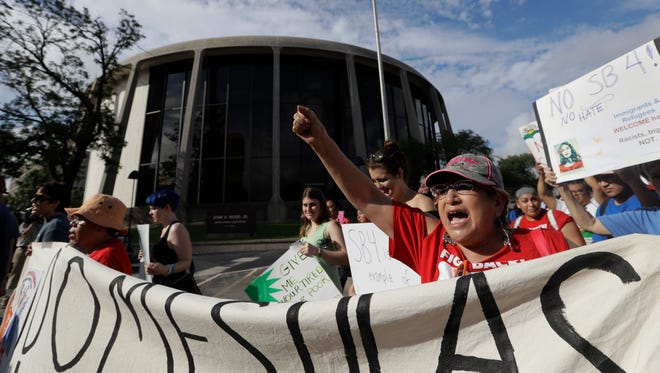 Protesters march Monday outside the Federal Courthouse in San Antonio to oppose a new Texas sanctuary cities law.