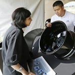 Joe Quinones, design engineer with Ford Motor Co., shows a carbon fiber wheel to Priyanka Karkhanis during groundbreaking ceremonies in June for the $50 million Indiana Manufacturing Institute. The Jobs Creation Committee issued preliminary findings earlier this month suggesting that the state end its licensing engineers.