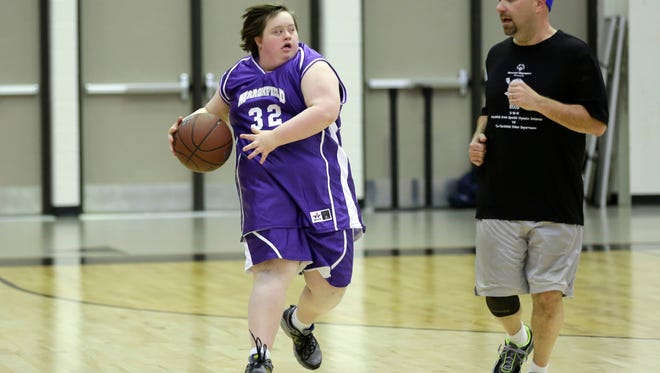 Mandy Yohn (32) runs downcourt racing Officer Bob Larsen during the Marshfield Area Special Olympics game against the Marshfield Police Department at Marshfield High March 18, 2016.