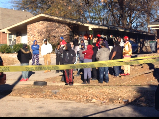 A crowd gathers near the scene of a shooting Friday,
