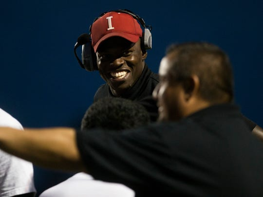 Immokalee head football coach Rodelin Anthony smiles in the huddle during the first half of action against Dunbar High School in a District 12 matchup Tuesday, October 17, 2017 in Immokalee, Fla.
