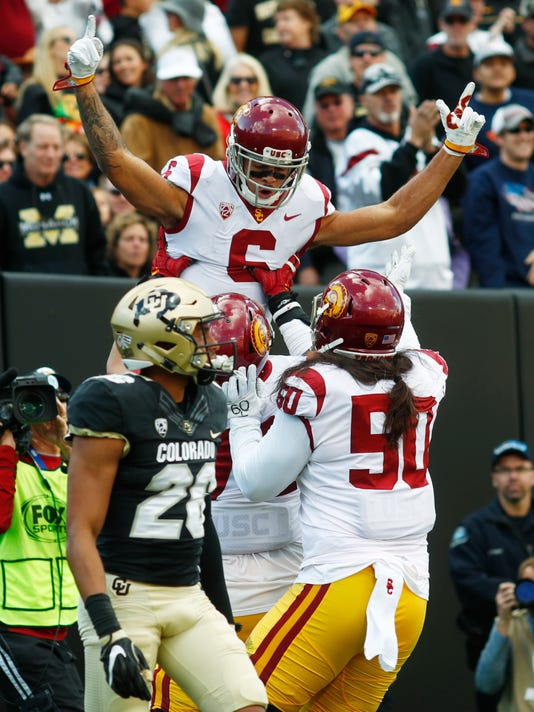 USC wide receiver Michael Pittman Jr., back top, raises his arms after his touchdown catch as center Nico Falah, back center, and linebacker Connor Murphy, back right, join in the celebration as Colorado defensive back Isaiah Oliver, front, walks away in the first half of an NCAA college football game Saturday, Nov. 11, 2017, in Boulder, Colo. (AP Photo/David Zalubowski)
