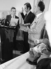 Beau Biden (foreground) plays near his father, Joe Biden (center) being sworn in as the U.S. senator from Delaware, by Senate Secretary Frank Valeo (left) in ceremonies in a Wilmington hospital. Beau was injured in an accident that killed his mother and sister in December 1972. Mrs. Biden's father, Robert Hunter, holds the Bible.