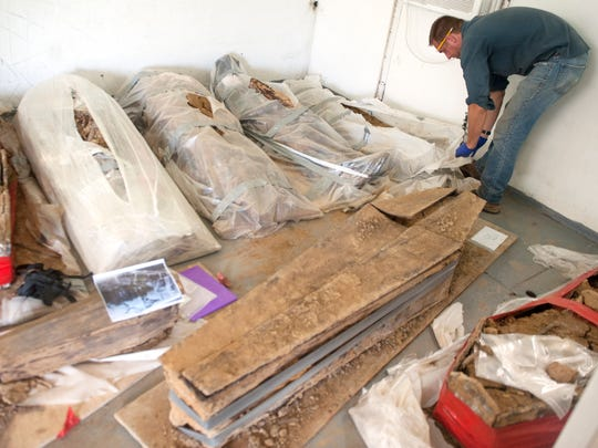 George Leader, a professor of sociology and anthropology at the College of New Jersey inspects one of the coffins discovered at a construction site in Old City, Philadelphia, as the remains are fully dug from their coffins and examined at a facility in Burlington County.  07.17.17