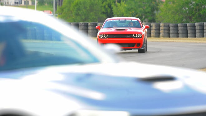 A Dodge Charger Hellcat and Challenger Hellcat are seen on the track.