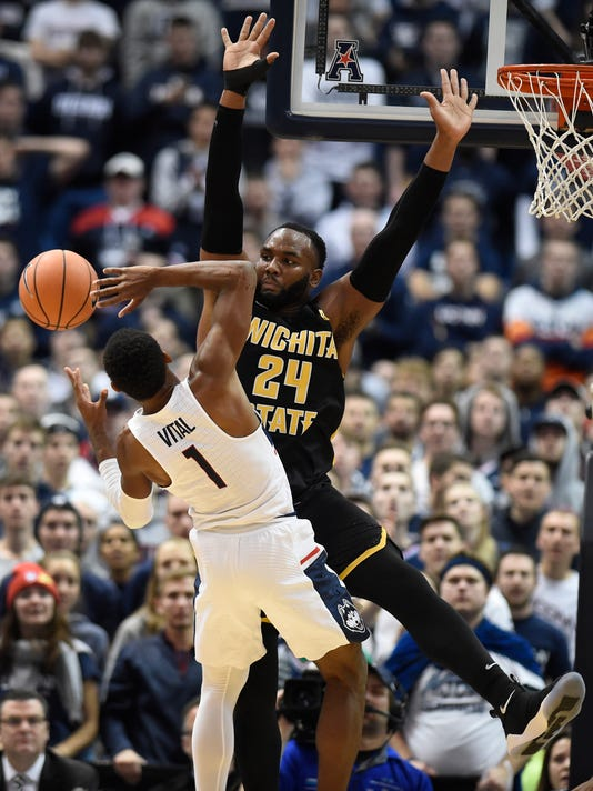 Wichita State's Shaquille Morris, right, fouls Connecticut's Christian Vital during the first half of an NCAA college basketball game, Saturday, Dec. 30, 2017, in Hartford, Conn. (AP Photo/Jessica Hill)