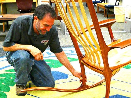 Woodworking teacher Josh Paul admires the joinery on Justin Fiaschetti's rocking chair.