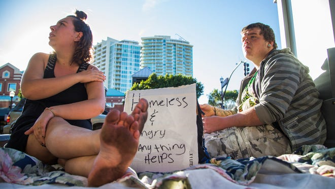 Vanessa Eley and Austin Webber panhandle on a sidewalk in downtown Tempe on Feb. 23, 2016.  A past effort to curb sidewalk campers caused a severe backlash, so the city pulled back, but now its pursuing another ordinance in response to more business complaints.