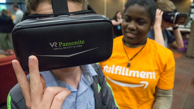 Michael Fabian tries virtual reality glasses, assisted by Amazon employee Chazz Horn.