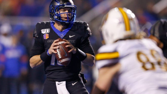 Boise State quarterback Chase Cord, left, looks down field against Wyoming during the second half of an NCAA college football game Saturday, Nov. 9, 2019, in Boise, Idaho. Boise State won 20-17. (AP Photo/Steve Conner)