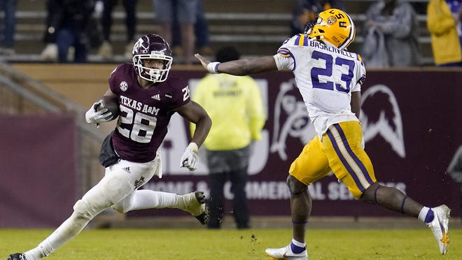 Texas A&M running back Isaiah Spiller tries to turn the corner as LSU linebacker Micah Baskerville tracks him during the Aggies' 20-7 win Saturday in College Station. Spiller ran for 141 yards and a touchdown in the victory.
