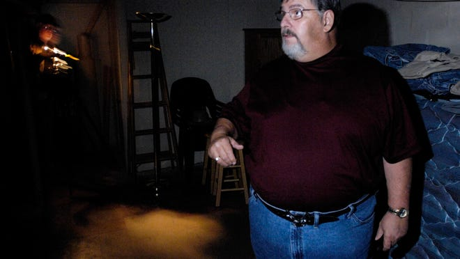 Rob Conover of Pekin stands in the spot where a double murder-suicide took place as he prepares to cleanse a house of the ghost of the murderer, said to be haunting the premises. Behind him, Bill Homel, also of Pekin, sets up a video camera to record any signs of paranormal activity that might be there during the cleansing, which Conover performs in total darkness. Conover claims that he was able to rid the house of the ghost.