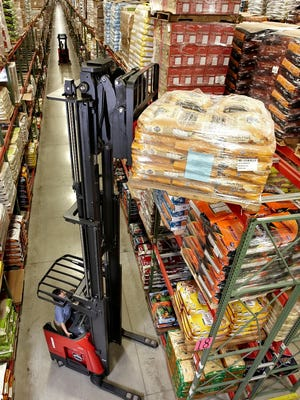Raymond's flagship forklift, the Raymond Reach-Fork® truck, places goods on a rack in a warehouse.