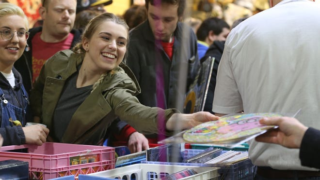 """Paige Babbage, Greece, center, kindly passes a """"Hello Kitty"""" album off to another shopper as she and friend Emily Baker, Greece, left, search through the bins of hundreds of records."""