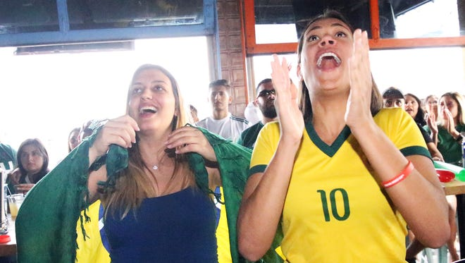 Brazil fans celebrate a goal against Mexico on Monday while watching the game at the Brass Monkey in El Paso.