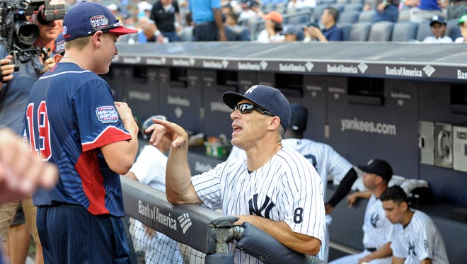 New York Yankees manager Joe Girardi talks with players from the 2016 Little League World Series Championship team from Endwell, New York prior to a baseball game against the Tampa Bay Rays Saturday, Sept. 10, 2016, at Yankee Stadium in New York.