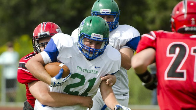 Colchester's Jared Antoniak (21) churns through a tackle during the third quarter of Saturday's game against Champlain Valley.