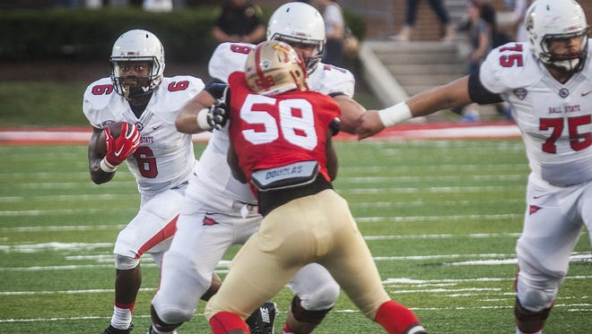 Offensive tackle Drake Miller and guard Vinnie Palazeti open a hole for Ball State's Teddy Williamson against VMI.