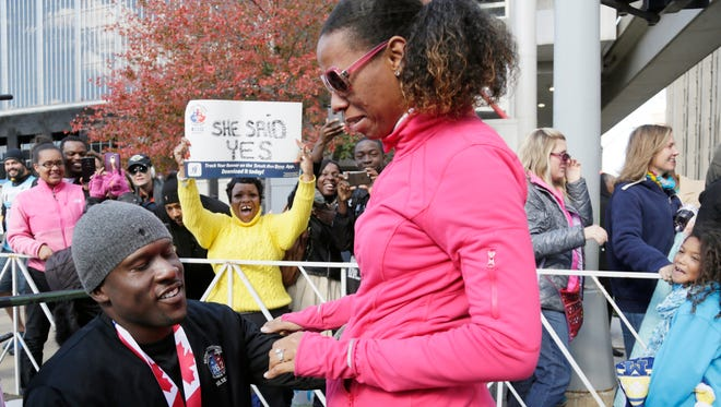 """'She Said Yes"""" and she did after Eric Rhymes, 39, of Detroit proposed to his long time girlfriend Zakyia Lumumba, 39, after he ran his first marathon at the 38th Detroit Free Press/Talmer Bank Marathon Sunday Oct. 18, 2015."""