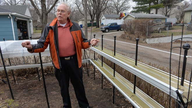 Gene Carlson tells on Wednesday, April 6, how he came up with the idea of creating a raised garden constructed from rain gutters and posts.