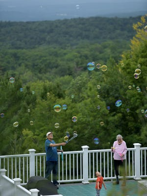 PRINCETON - Rick and Claudia Rys entertain their grandson, Joseph, 4, with bubbles from their deck, with a long view toward Boston, on Sunday.