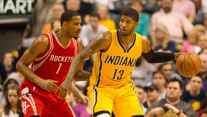 Indiana Pacers forward Paul George dribbles the ball in on defending Houston Rockets forward Trevor Ariza.