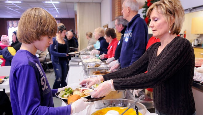 Heidi Richards serves up a meal to a volunteer before passing it out Saturday afternoon at a community dinner a the First Congregational Church in Port Huron.