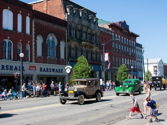 Kids go chasing after candy while classic cars drive through downtown Marshall during their Memorial Day Parade.