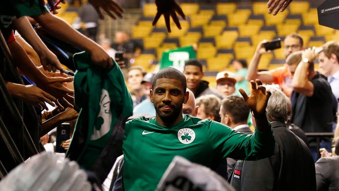 Boston Celtics guard Kyrie Irving (11) leaves the court after a 94-82 win over the Charlotte Hornets in a preseason game at TD Garden.