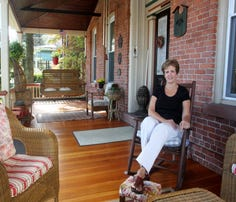 Michelle Natale, owner of the Bricktown Inn in Haverstraw, sits on the front porch.