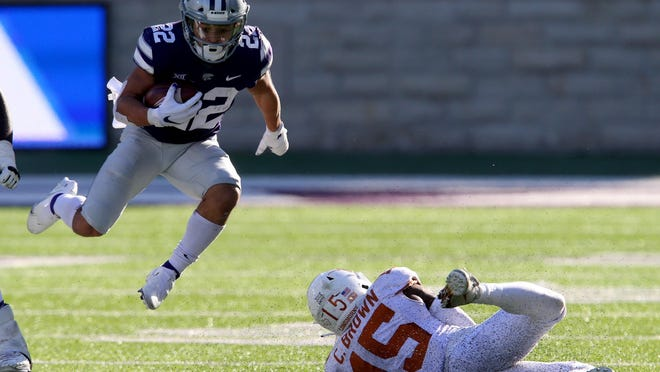 Kansas State running back Deuce Vaughn (22) jumps over the  Texas defensive back Chris Brown (15) during Saturday's game at Bill Snyder Family Stadium.