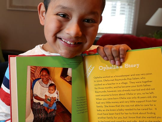 Noah Geppert holds a book with a photo of his birth mother Ofelia.