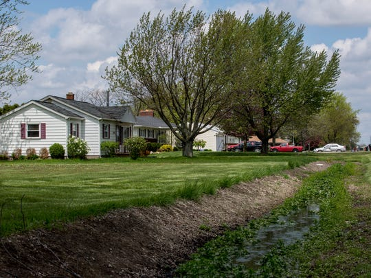 Water runs through a drainage ditch in front of homes