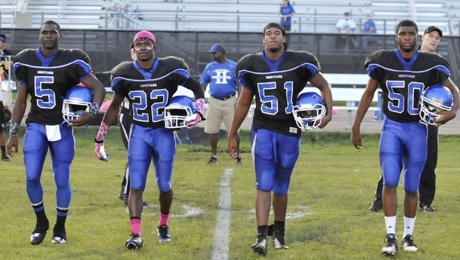 The Heritage Panthers team captains take the field before a prep football game against the Port St. Lucie Jaguars at Heritage High Stadium on Friday.
