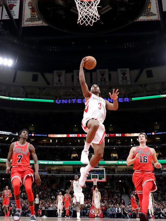 Houston Rockets' Chris Paul (3) scores between Chicago Bulls' Justin Holiday (7) and Paul Zipser during the second half of an NBA basketball game Monday, Jan. 8, 2018, in Chicago. (AP Photo/Charles Rex Arbogast)
